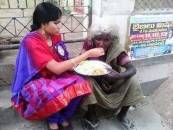 Girl feeding food for poor women